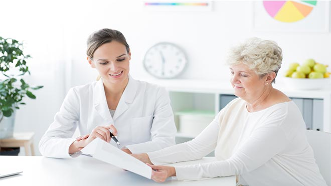 Two women sitting in a dietician's office and talking about a new diet plan
